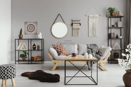 Photo for Stylish wooden coffee table in the middle of warm ethno living room with patterned pillow and blanket on comfortable scandinavian couch, real photo - Royalty Free Image