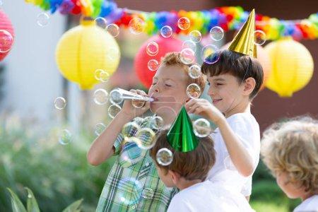 Foto de Celebrando el cumpleaños de su amigo durante la fiesta en el jardín de niños - Imagen libre de derechos