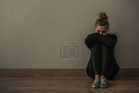 Photo for Young woman with anxiety disorder wearing dark clothes sitting on the floor, copy space on empty wall - Royalty Free Image