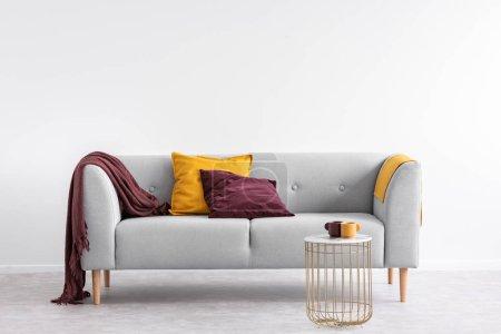 Photo pour Oreillers et couverture violette sur canapé gris dans le salon blanc intérieur avec table dorée. Une vraie photo - image libre de droit