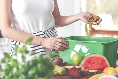 Photo for Closeup of eco friendly woman in the kitchen disposing of leftovers of kiwi into compost bin while preparing fruit salad - Royalty Free Image