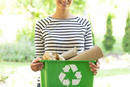 Photo pour Belle femme souriante avec un conteneur de recyclage vert avec des déchets de papier - image libre de droit