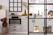 Elegant bright kitchen interior with white cupboards and black shelf