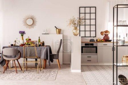 Photo pour Élégante cuisine ouverte et salle à manger intérieure avec placard blanc et longue table avec nappe grise et nourriture - image libre de droit