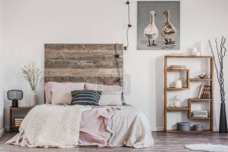 Photo pour Mignon poster avec deux canards sur le mur blanc de l'intérieur de la chambre de bon goût avec lit avec literie rose pastel - image libre de droit