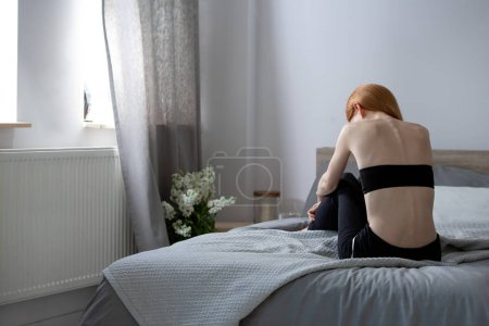 Photo for Anorexic woman sitting on a bed in a bedroom - Royalty Free Image