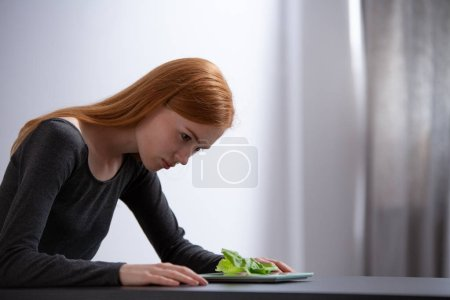 Photo for Young girl looking at the salad on a table - Royalty Free Image