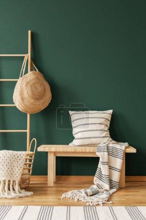 Photo pour Oreiller sur tabouret en bois à côté de l'échelle avec sac dans le salon intérieur vert avec tapis. Une vraie photo - image libre de droit