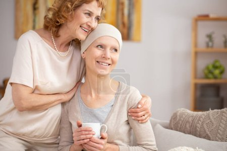 Photo pour Femme âgée souffrant d'un cancer du poumon assise à la maison avec sa sœur leur enjoignant de travailler après un traitement hospitalier - image libre de droit