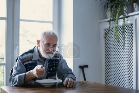 Photo for Senior grandfather with grey hair and beard sitting alone in the kitchen eating breakfast - Royalty Free Image