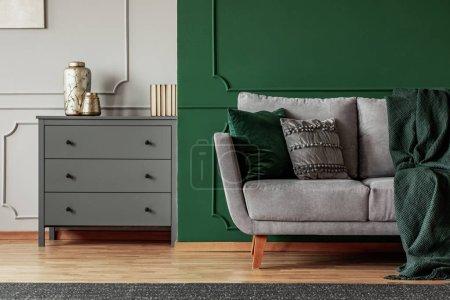 Photo pour Mur vert, canapé scandinave gris et commode en bois dans un élégant salon intérieur - image libre de droit