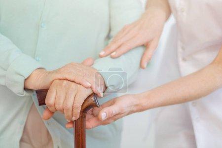 Photo pour Gros plan des mains de la femme âgée sur la canne en bois, médecin serviable la soutenant - image libre de droit