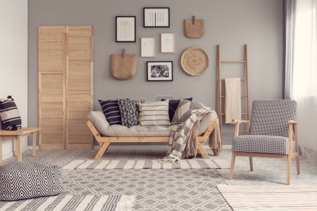 Photo for Trendy vintage armchair next to chic scandinavian sofa with pillows in classy living room interior - Royalty Free Image