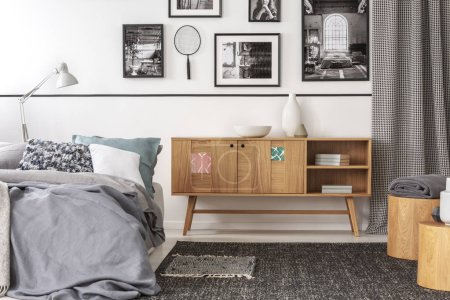 Photo for Vintage wooden cupboard next to king size bed with pillows and blanket in trendy bedroom interior - Royalty Free Image