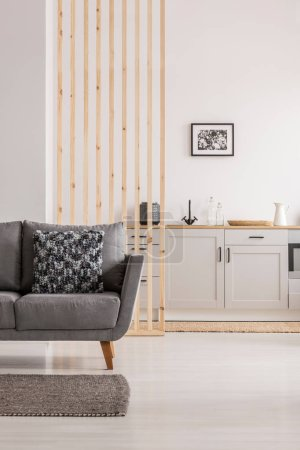 Photo for Open plan living room and kitchen interior with white cupboards and grey sofa with pillows - Royalty Free Image