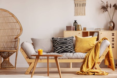 Photo for Stunning wicker peacock chair next to modern scandinavian settee with pillows - Royalty Free Image