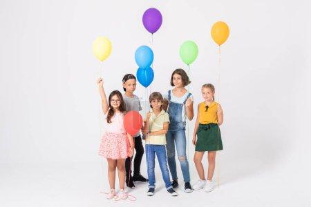 Photo pour Heureux écoliers garçons et filles tenant des ballons colorés - image libre de droit