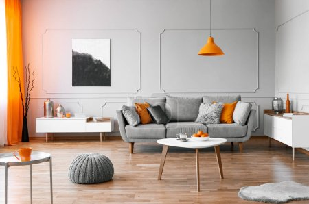 Stylish coffee table with kinck knacks in front of elegant couch with pillows