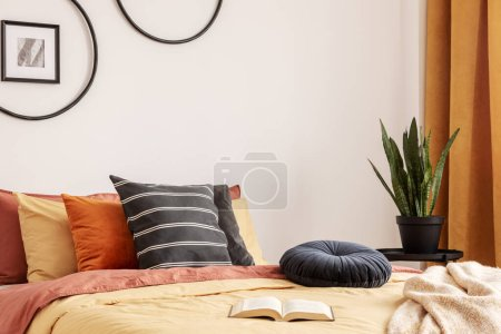 Photo pour Oreiller en velours rond noir sur couette jaune dans une chambre à coucher tendance avec lit king size. - image libre de droit