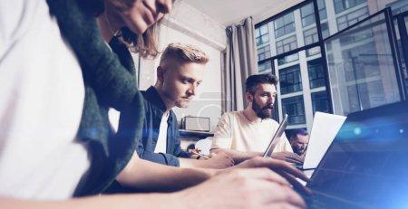 Foto de Profesionales de negocios en momentos de trabajo. Grupo de jóvenes coworking confiados que analizan los datos utilizando la computadora mientras pasan tiempo en la oficina. Amplio - Imagen libre de derechos