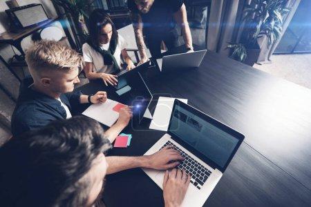 Photo pour Moments de travail. Groupe de personnes de jeunes collaborateurs en vêtements intelligents discutant affaires alors qu'il travaillait au bureau créatif - image libre de droit