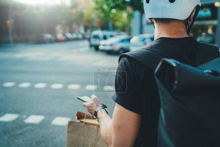 Photo pour Man courier à l'aide d'une application de carte sur téléphone mobile pour trouver l'adresse de livraison dans la ville. Anonimous Courier livraison de nourriture à la maison - image libre de droit
