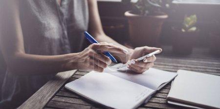 Photo pour Jeune femme d'affaires assise à table sur la terrasse de la caféine et prenant des notes dans un carnet. Apprentissage étudiant en ligne ou concept de blogueur - image libre de droit