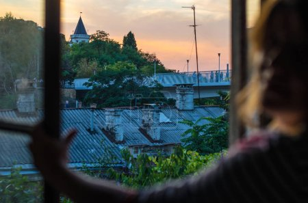 Photo for Close-up of woman opening window with view of old roofs and town at sunset - Royalty Free Image