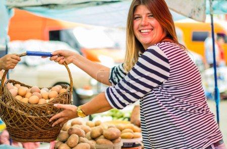 Photo pour Panier de tenue de femme d'oeufs frais crus au marché fermier de sourire - image libre de droit