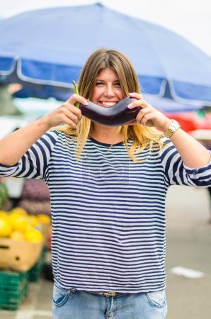 Photo for Smiling young woman holding fresh aubergine at farmer market - Royalty Free Image