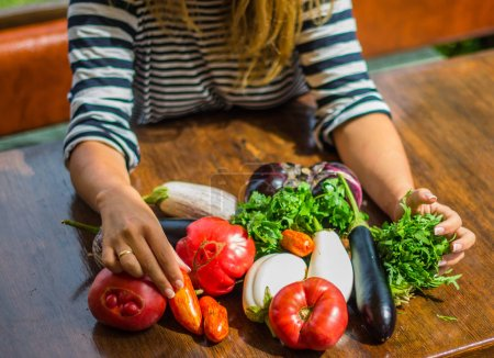Photo for Woman sitting with heap of fresh vegetables on wooden table - Royalty Free Image