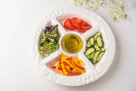 Photo for Fresh sliced vegetables with olive oil in dish on white surface - Royalty Free Image