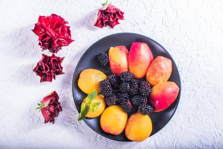 Photo for Fresh fruits and berries on plate on white background with flowers - Royalty Free Image