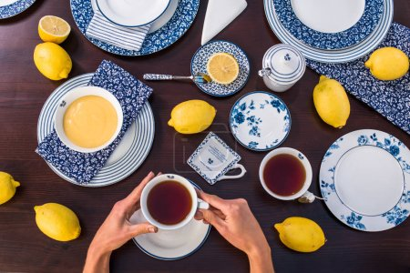 Photo for Human hands holding cup of tea with lemon curd on table - Royalty Free Image