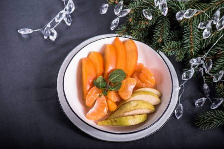 Photo for Fresh pieces of persimmon, apple and mandarin on plate with christmas decor on background - Royalty Free Image