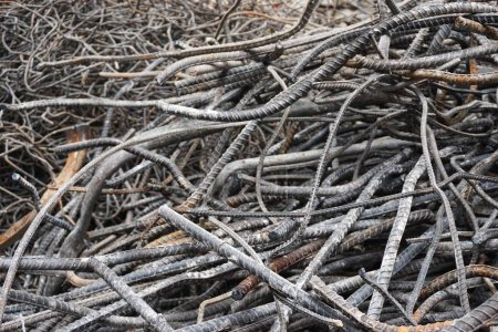 Mangled steel rebar waiting to be recycled at a building demolition site in urban Hanoi Vietnam. The metal will be melted down and made into new products.