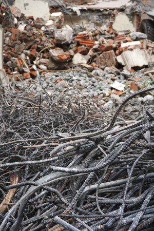 Tangled steel rebar with rubble behind at a construction demolition site in Hanoi Vietnam. The metal will be recycled and made into new products.