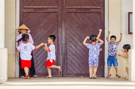 Cai Be, Vietnam - 6 April, 2018: Laughing children playing and romping around under the supervision of a school teacher at the entrance of a cathedral