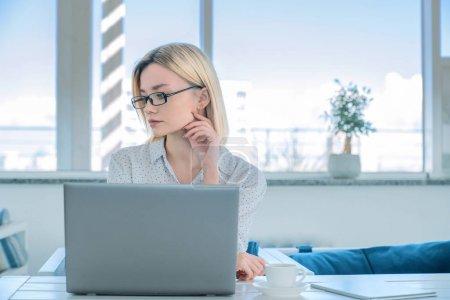 Photo pour Vue de face prise de jeune femme caucasienne réfléchie dans des lunettes avec le regard tourné vers l'extérieur assis au-dessus de la table de travail avec ordinateur portable sur elle en lieu de coworking . - image libre de droit