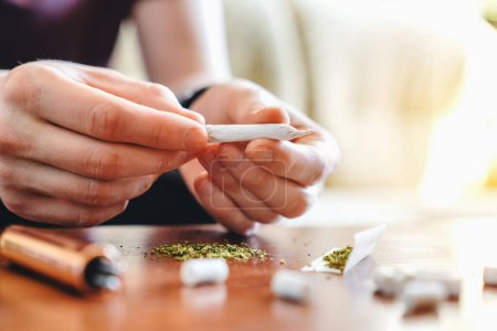 Photo for Cropped shot of young man making marijuana joint - Royalty Free Image