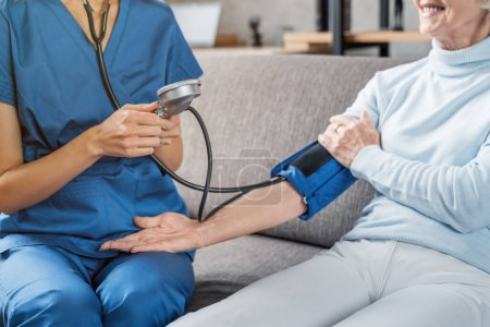 Photo for Cropped image of medical assistant measuring female patient blood pressure - Royalty Free Image