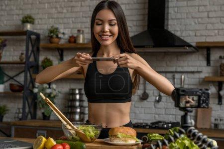 Photo pour Blogueuse souriante faisant la photo d'aliments sains sur la table de cuisine - image libre de droit