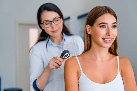 Photo pour Médecin féminin vérifiant la peau de la fille avec dermatoscope dans une clinique - image libre de droit