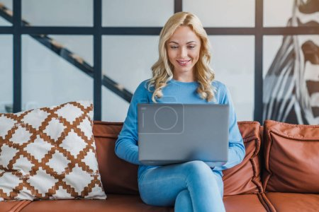 Photo for Young woman working on laptop computer while sitting on sofa at home - Royalty Free Image