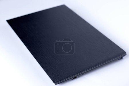 Photo pour Ordinateur portatif noir sur le fond blanc se ferment vers le haut - image libre de droit