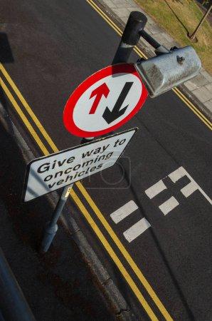Photo pour Une vue inhabituelle du haut d'un panneau de signalisation qui demande au conducteur de céder le passage aux véhicules venant en sens inverse. - image libre de droit