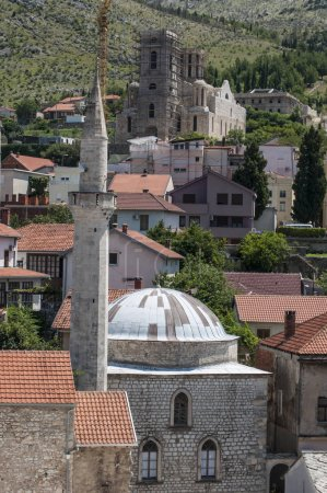 Mostar, 06/07/2018: view of the Clock Tower (Sahat Kula), example of the prolic Ottoman period, dated 1630, bombed and damaged during the Bosnian War (1992-1995), and a mosque with its minaret