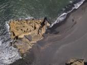 Aerial view of waves crashing on a rock formation. Playa El Golfo. Black beach of the Charco de los Clicos. Lanzarote, Canary Islands, Spain