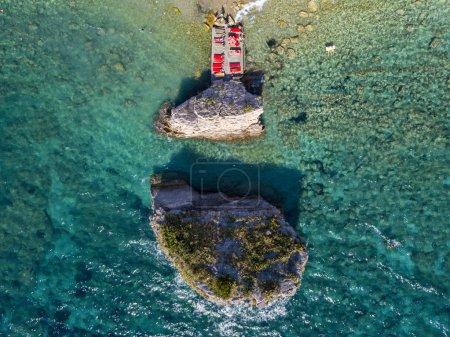 Photo pour Vue aérienne de Sveti Nicola, île de Budva, Monténégro. Plage d'Hawaï, parasols et baigneurs et eaux cristallines. Côtes déchiquetées avec des falaises abruptes surplombant la mer transparente. Nature sauvage et maquis méditerranéen - image libre de droit