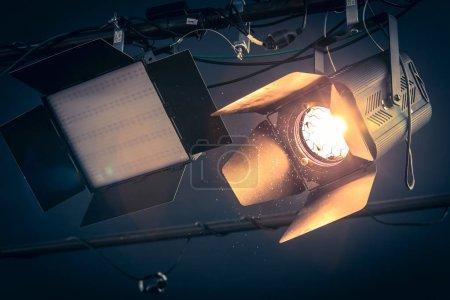 Photo pour Projecteur professionnel de studio orange suspendu au plafond. Particules de poussière et fusées éclairantes . - image libre de droit
